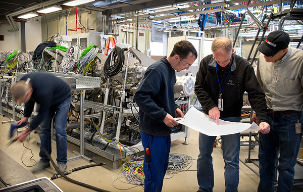Engineers and technicians from Ampulse, NREL, and Roth & Rau go over plans for installing parts in the pilot production line for making solar cells via a chemical deposition process - image credit: Dennis Schroeder/NREL