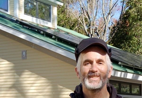 Dave Enos of Bedford, Mass., in front of his addition and 10-kw PV array that will provide the energy for all of his home's heat and hot water. (image via Green Tech Advocates)