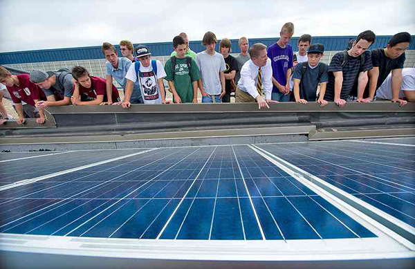 "Chatfield High School teacher Joel Bertelsen explains the fundamentals of a photovoltaic array to his Intro to Engineering Students on the school's roof. NREL sponsors the ""Solar on Schools"" program that has been adopted by Jeffco Public Schools, the largest district in Colorado. Image Credit: Dennis Schroeder/NREL"