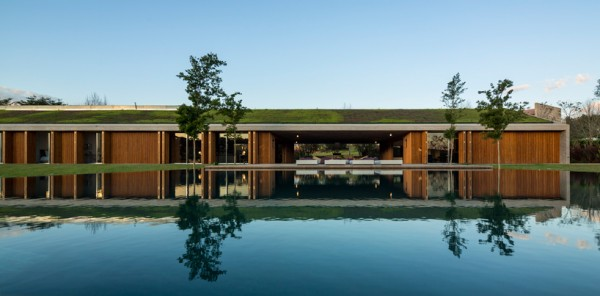 Retractable wooden doors, reflected in pool on main patio. Image via Studio MK27.