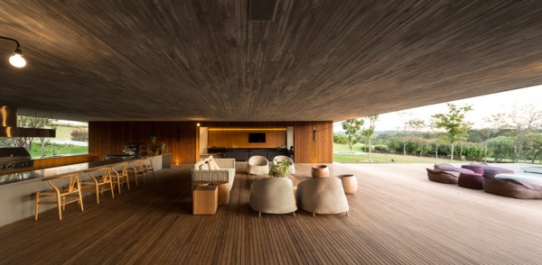 Living room open to the elements under massive concrete roof. Image via Studio MK27.