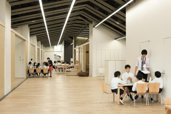 Interior of school, showing the open seating areas and enclosed school rooms under a long, continuous roof. Image via Kengo Kuma and Associates.