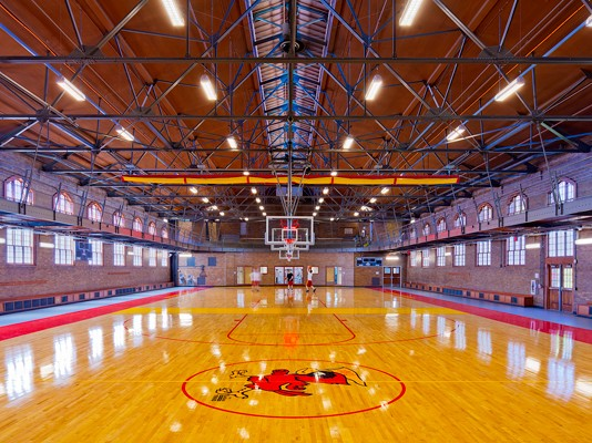 The State Gym's new basketball court, which reused most of the wood flooring from the original building. Image via RDG Planning & Design.