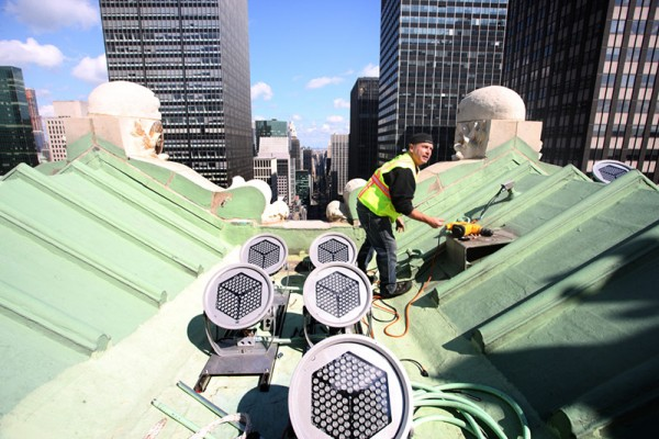 A worker installs some of the multicolored Lumenplus LED lamps on the roof of the Helmsley Building. Image by Ed Lederman via Monday Properties.