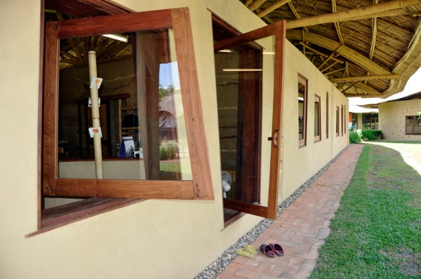 Glass windows and doors open on a pivot to allow easy ventilation in the tropical climate. Image via Panyaden School.