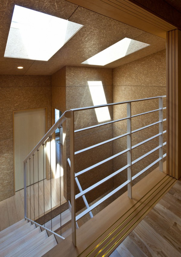Skylights draw natural light into the stairwell, lined with exposed OSB and hardwood floors. Image by Stirling Elmendorf via Shuhei Endo.
