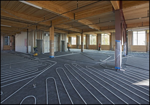 Interior view showing the timber ceilings and hydronic tubing for the embedded solar-powered radiant heating system prior to the concrete pour. Image via Bullitt Foundation.