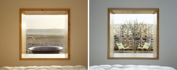 Window views of wind turbines and recycled wooden palette wind breaks. Image via Hotel Aire de Bardenas.