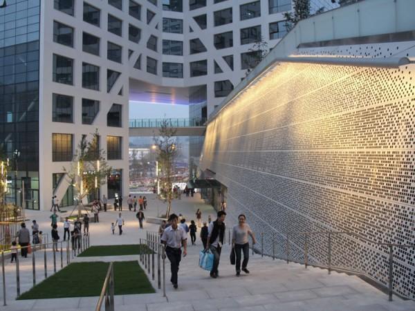 The perforated skin of the central shopping complex is lit up in the evening. Image via Steven Holl Architects.