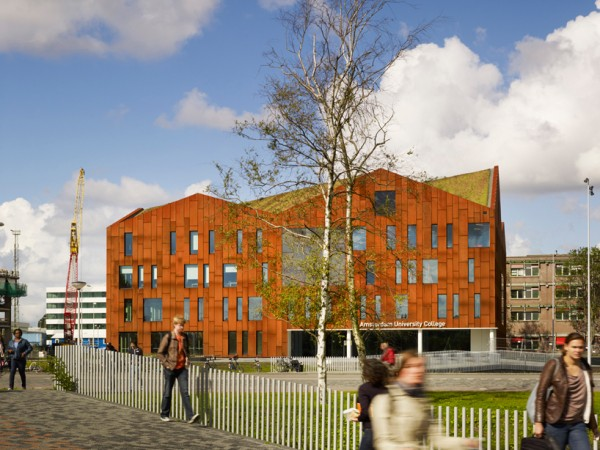 The new Amsterdam University Colege building, showing its angled green roof. Image via Mecanoo.