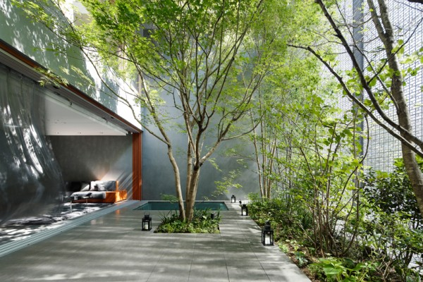 A private tree garden acts as a buffer between the living room (left) and the glass masonry wall (right) facing the street. Image by Koji Fujii / Nacasa & Partners, via Hiroshi Nakamura & NAP.