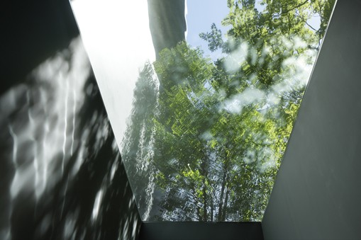 View of second-story courtyard through transparent reflecting pool, as seen from the house's ground-floor entryway. Image by Koji Fujii / Nacasa & Partners, via Hiroshi Nakamura & NAP.