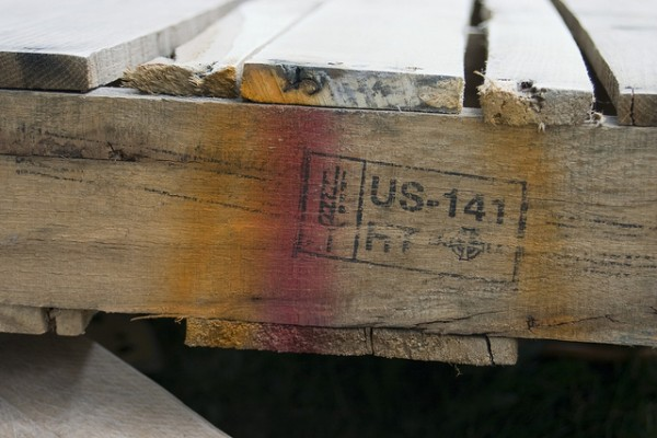 "A wood pallet displaying the ""HT"" logo, indicating that it has been heat-treated to remove food-borne pathogens. Image by Lori Danelle via Flickr."