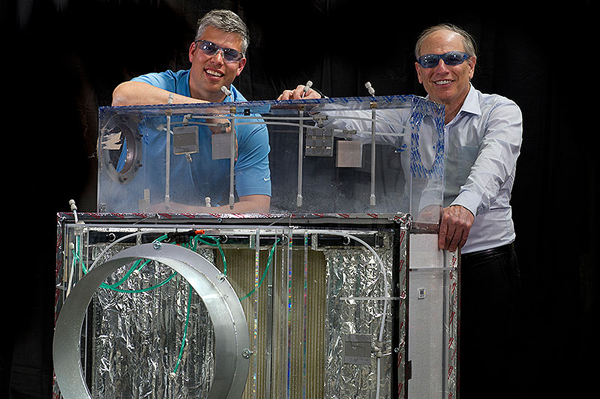 Eric Kozubal, left, and Ron Judkoff stand next to a first-generation prototype DEVAP air conditioner. The new technology predicts an energy savings of 40% to 80% for light commercial buildings. Jason Woods and Jay Burch, also members of the DEVAP team, are not pictured. (image credit: Dennis Schroeder/NREL)