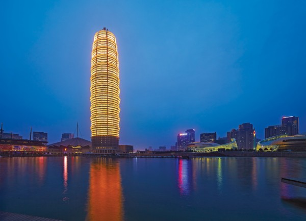 The recently completed Greenland Tower in Zhengzhou, China, shines brightly at night with its reflective window panels. Image via SOM.
