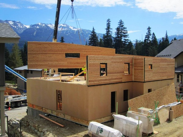 The Rainbow House under construction, showing the prefab super-insulated panel walls being lowered into place. Image via Marken Projects.