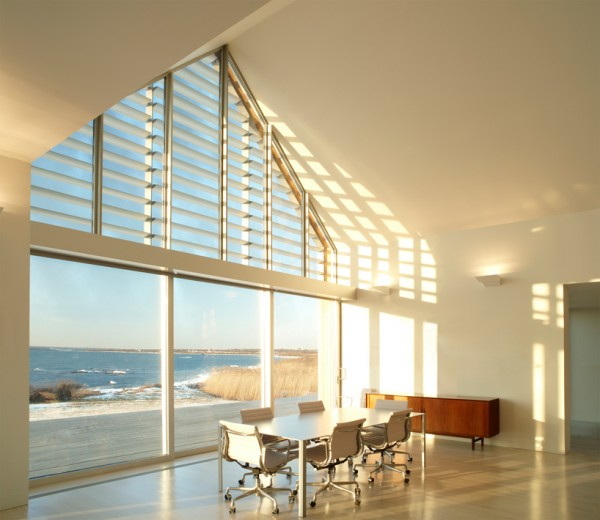 View of sunlit interior, showing gorgeous beach vistas and louvered slats to reduce solar gain. Image by Michael Biondo via Roger Ferris + Partners.