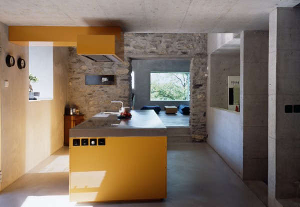 A view of the kitchen shows the blending of the old masonry and new concrete elements. Image by Thomas Jantscher via Savioz Fabrizzi Architectes.