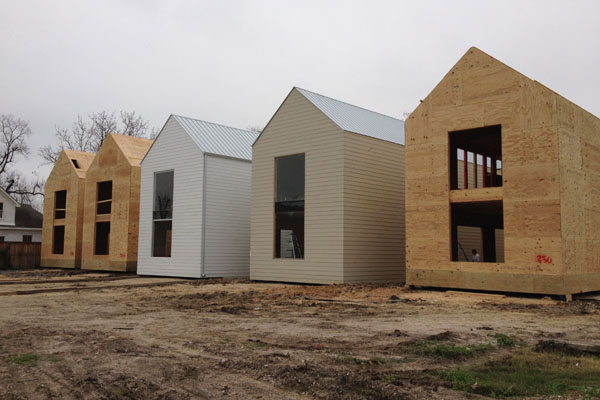 Row on 25th homes under construction, showing the basic wood frame and plywood. Image via Shade House Development.
