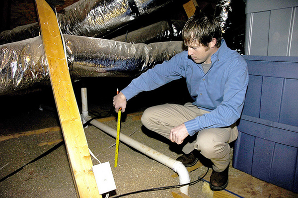 United Energy Conservation Coordinator Seth Rosser measures insulation as part of an energy audit at a member's home. (image via USDAgov/Flickr)