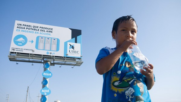 A boy enjoys a drink of filtered water harvested from the billboard behind him. Image via UTEC.