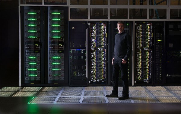 Steve Hammond, director of NREL's Computational Science Center, poses by servers in the HPC data center. Image by Dennis Schroeder via NREL.