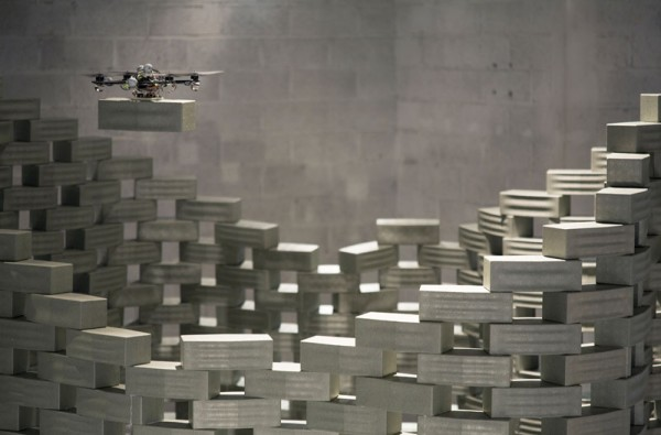 A quad-copter drone positions a foam brick over a prefab model tower in a 2012 demonstration. Image by François Lauginie via Gramazio & Kohler Architekten.
