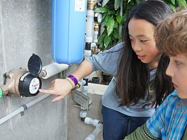 Students monitor the school's energy consumption gauges. Image via Bertschi School.