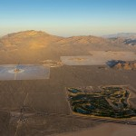 Aerial view of the Ivanpah Solar Power Facility at sunrise, with left to right Tower 1, 2 and 3, and the Primm Golf Course, bottom. (image via BrightSource Energy)