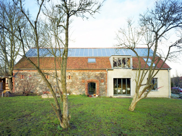 The rammed-earth extension on this stone farmhouse is the first use of the ancient technology in Germany since the 1950s. Image via Roswag Architekten.