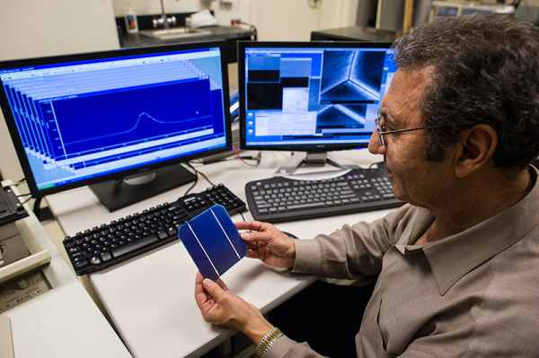 NREL Principal Scientist Mowafak Al-Jassim holds a TetraSun PV cell in the cathodoluminescence lab at NREL. The TetraSun cell combines increased efficiency and low cost, breaking the usual rules for solar cells. (image credit: Dennis Schroeder/NREL)